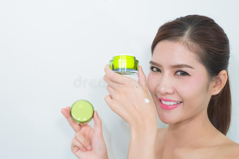 Mujer asiática hermosa que usa un producto para el cuidado de la piel natural, moistur fotografía de archivo