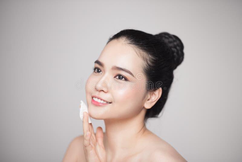 Mujer asiática hermosa sonriente feliz que usa el cojín de algodón que limpia a SK imagen de archivo