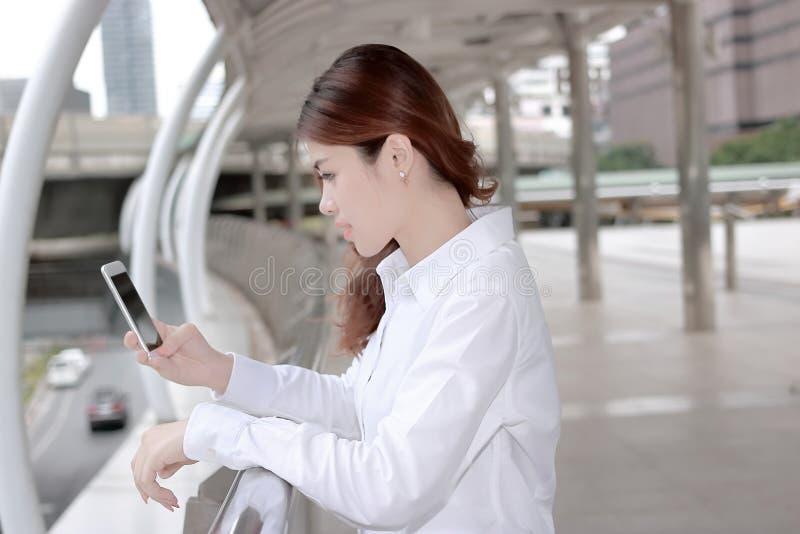 Mujer asiática joven atractiva que considera en el teléfono elegante móvil en sus manos la construcción del fondo urbano foto de archivo libre de regalías