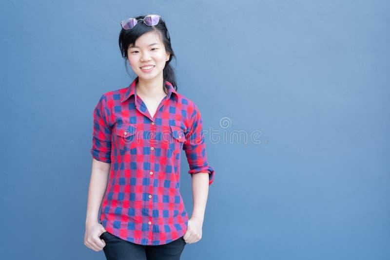 Mujer asiática joven atractiva que lleva la ropa de moda y las gafas de sol en el pelo que presenta en fondo azul de la pared de  imagen de archivo