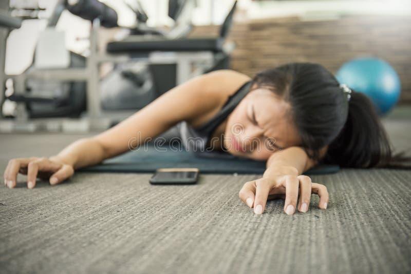 Mujer asiática joven atractiva que se resuelve con la máquina del ejercicio en el gimnasio imagen de archivo