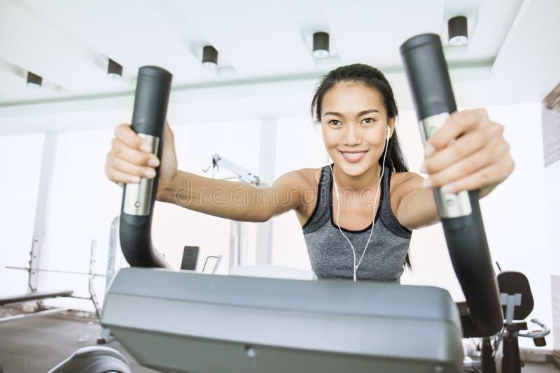 Mujer asiática joven atractiva que se resuelve con la máquina del ejercicio en el gimnasio fotografía de archivo libre de regalías