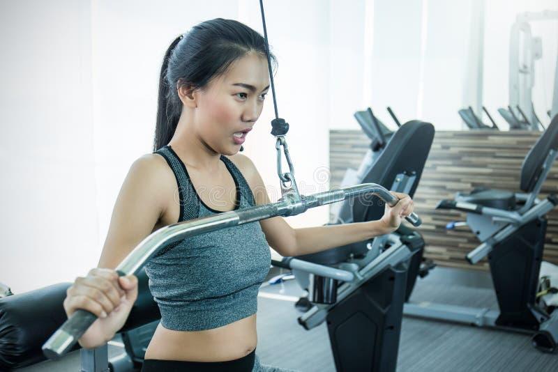 Mujer asiática joven atractiva que se resuelve con la máquina del ejercicio en el gimnasio imagenes de archivo