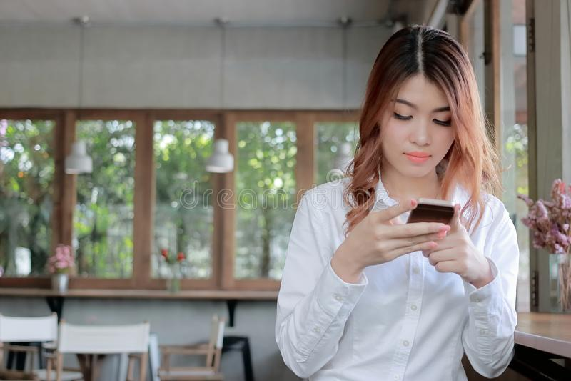 Mujer asiática joven atractiva que sostiene el teléfono elegante móvil en fondo moderno de la sala de estar imagen de archivo libre de regalías