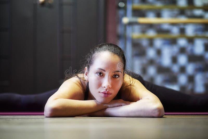 Mujer asiática joven bonita que miente en el piso y que hace la guita muchacha que hace ejercicio físico y que estira las piern imágenes de archivo libres de regalías