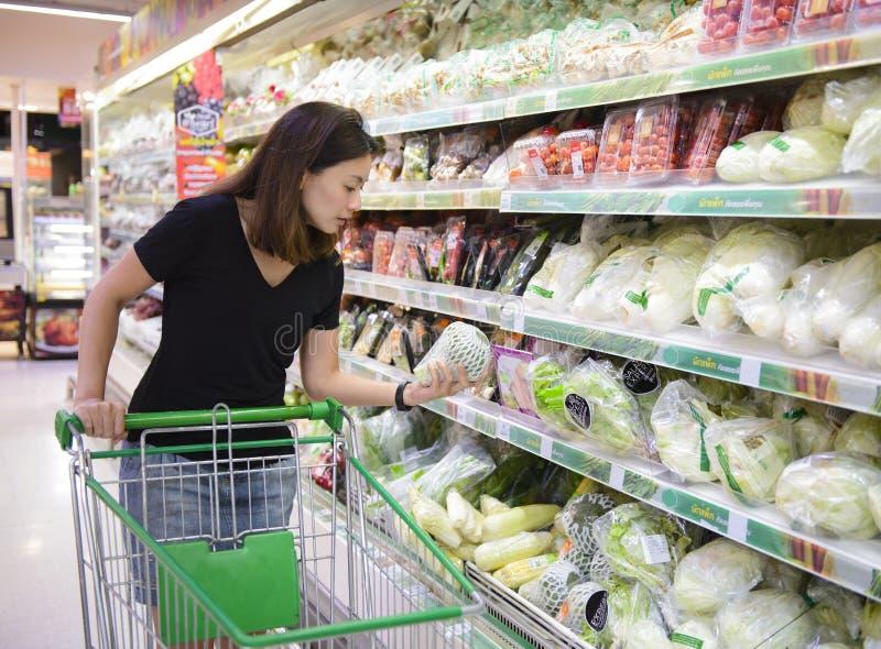 Mujer asiática joven con el carro de la compra que elige productos en supermercado fotos de archivo libres de regalías