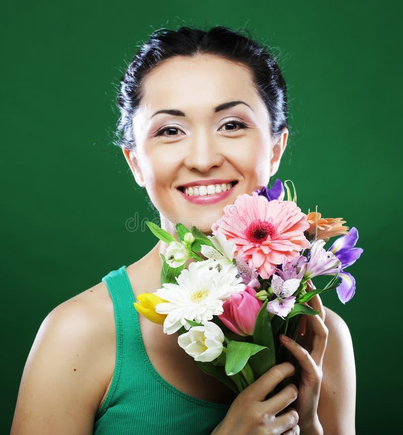 Mujer asiática joven con las flores del ramo foto de archivo libre de regalías