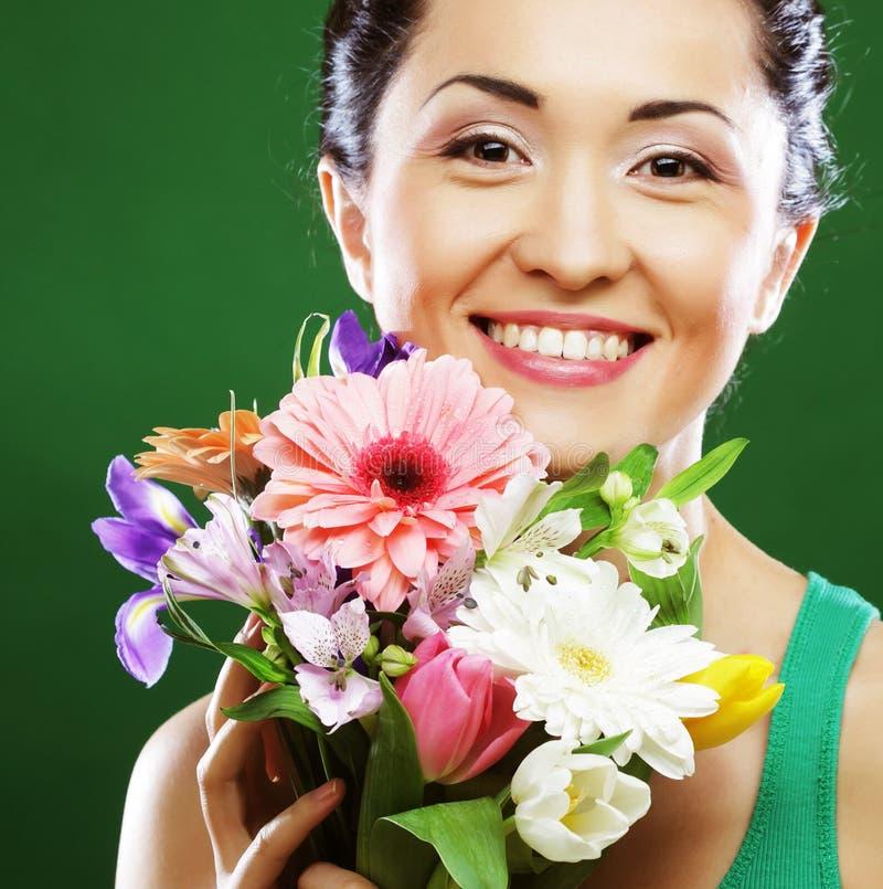Mujer asiática joven con las flores del ramo fotos de archivo