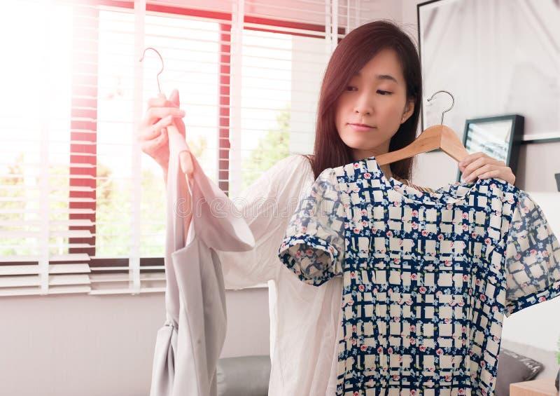 Mujer asiática joven confusa que intenta elegir los vestidos que se colocan en el cuarto imágenes de archivo libres de regalías