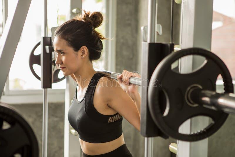 mujer asiática joven de la aptitud en ropa de deportes que ejercita los músculos constructivos que levantan el peso con el barbel foto de archivo