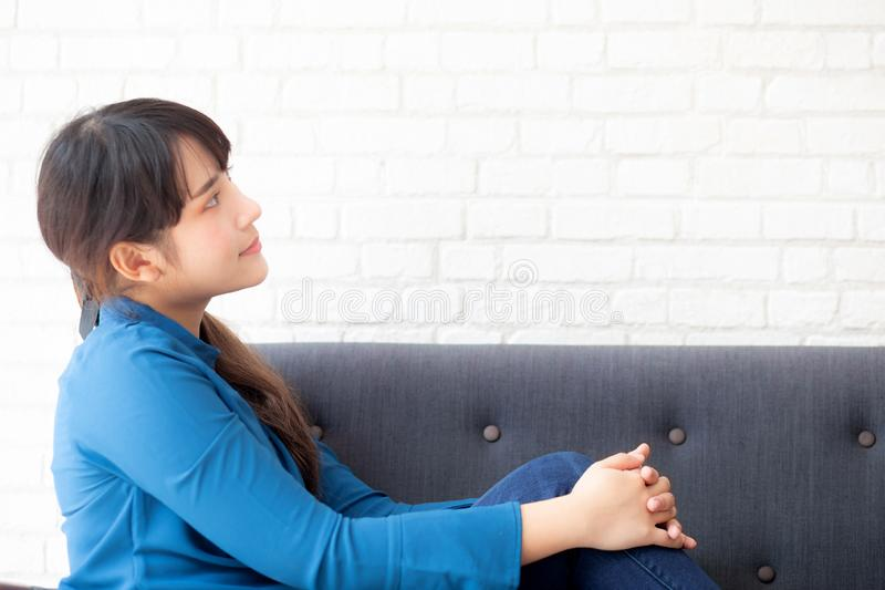 Mujer asiática joven del retrato hermoso que se sienta y que sonríe feliz y que mira algo en el sofá que muestra futuro o planifi imágenes de archivo libres de regalías