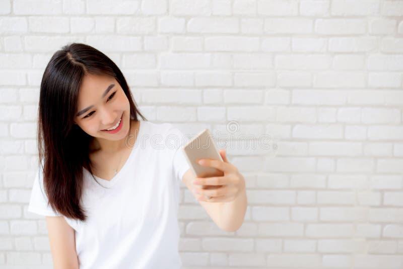 Mujer asiática joven del retrato hermoso que toma un selfie con el teléfono móvil elegante en fondo concreto del blanco del cemen fotos de archivo libres de regalías