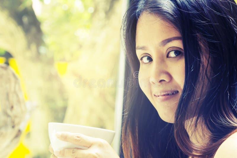 Mujer asiática joven del retrato que bebe el latte caliente del té verde en coffe imagen de archivo libre de regalías
