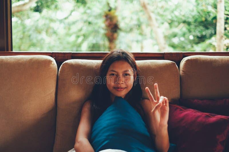 Mujer asiática joven durante las vacaciones que se relajan en el sofá con la ventana grande detrás de ella mujer el vacaciones de foto de archivo