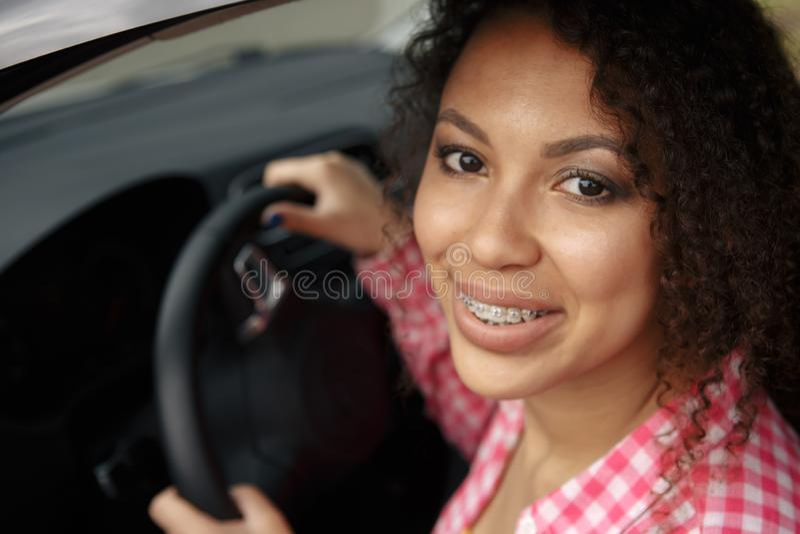 Mujer asiática joven en coche El conductor moderno de la chica joven conduce un coche y mira lejos con una sonrisa con los apoyos foto de archivo libre de regalías