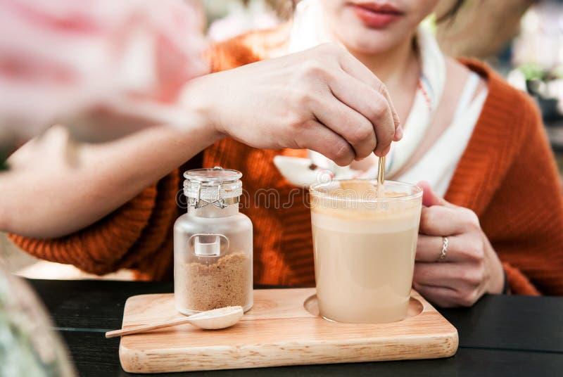 Mujer asiática joven en el suéter que revuelve el café caliente del latte en vidrio fotografía de archivo libre de regalías