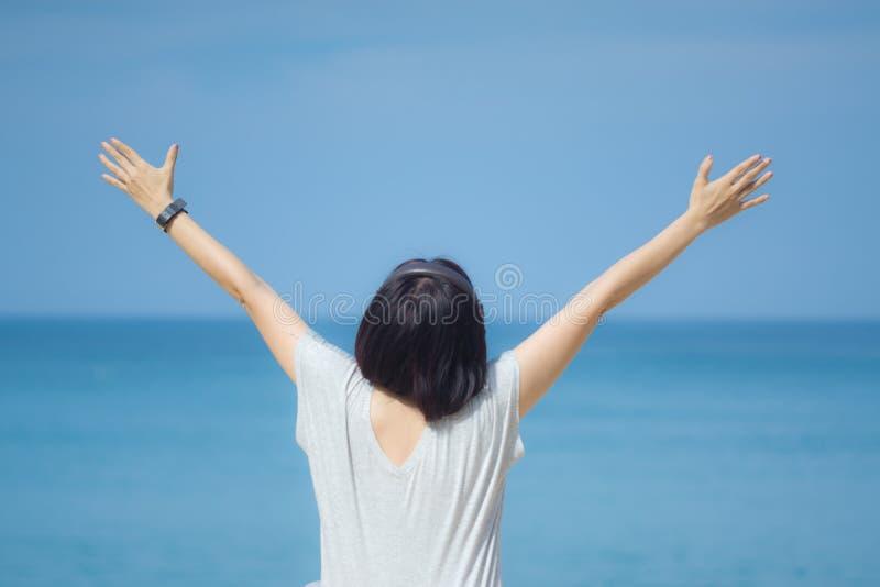 Mujer asiática joven en un vestido gris que lleva a cabo las manos hasta el cielo Cielo azul y mar cristalino de la playa tropica foto de archivo libre de regalías