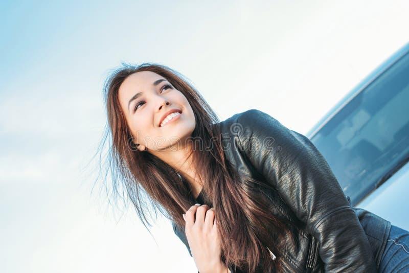 Mujer asiática joven encantadora hermosa del pelo largo moreno de Happpy en chaqueta de cuero negra cerca de su coche imagen de archivo