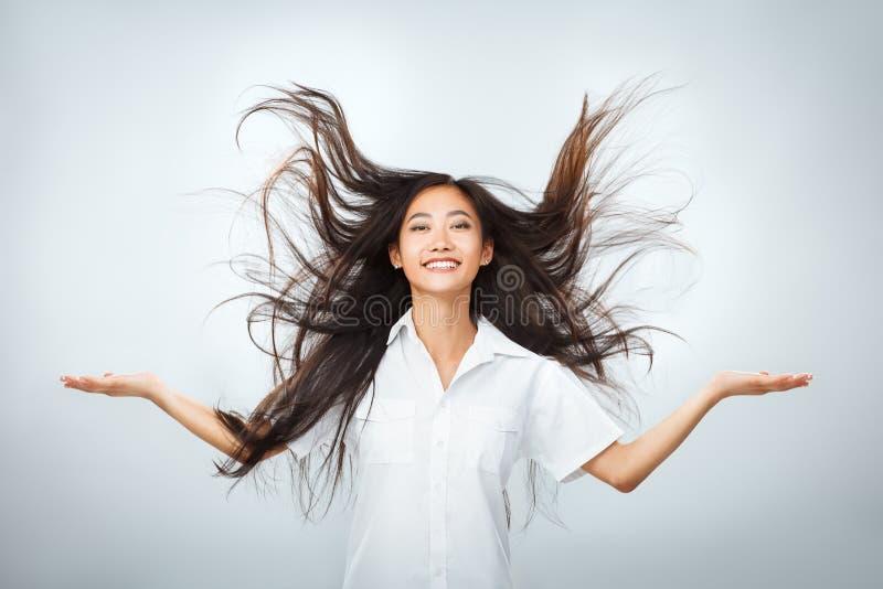 Mujer asiática joven feliz con el pelo largo del vuelo hermoso imagenes de archivo