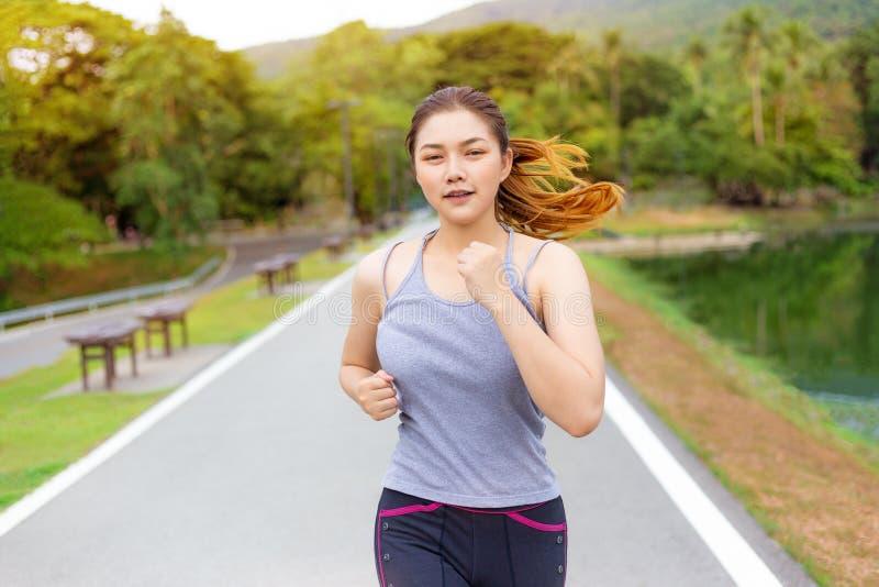 Mujer asiática joven feliz hermosa que corre para su ejercicio de la mañana fotografía de archivo libre de regalías