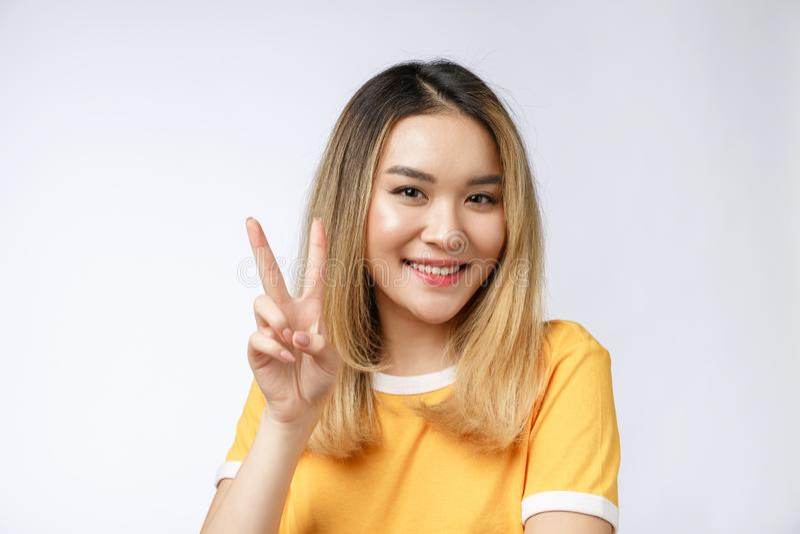 Mujer asiática joven feliz que muestra dos fingeres o gestos de la victoria con el área en blanco del copyspace para el texto, re foto de archivo