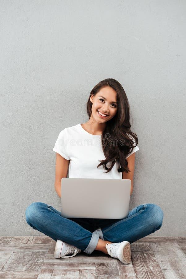 Mujer asiática joven feliz que trabaja en el ordenador portátil fotos de archivo libres de regalías