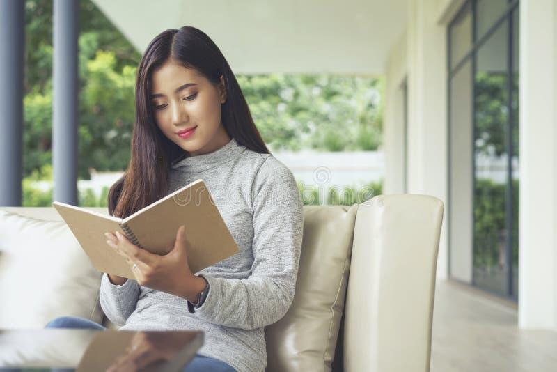 Mujer asiática joven gozar a leer la nota en un cuaderno, sentándose en el sofá en casa conceptos de sensación de la relajación fotografía de archivo libre de regalías