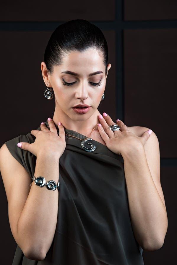 Mujer asiática joven hermosa con los pendientes y el collar elegantes fotografía de archivo libre de regalías