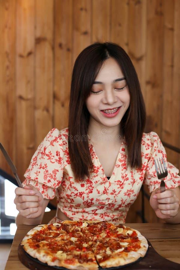 Mujer asiática joven hermosa que come la pizza deliciosa o deliciosa foto de archivo