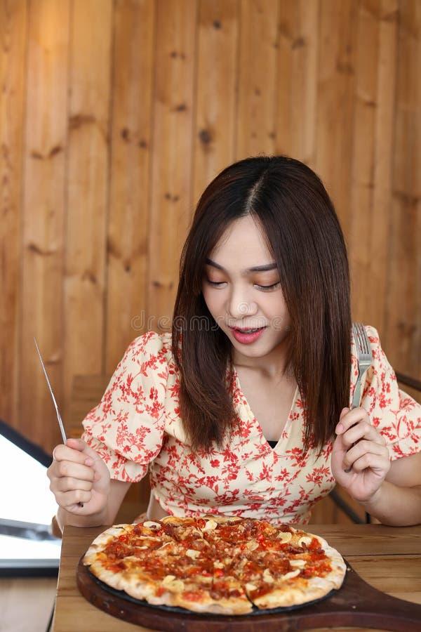 Mujer asiática joven hermosa que come la pizza deliciosa o deliciosa foto de archivo libre de regalías