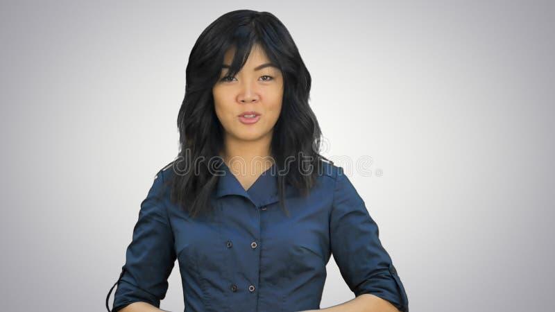 Mujer asiática joven hermosa que hace una presentación en el fondo blanco fotografía de archivo libre de regalías
