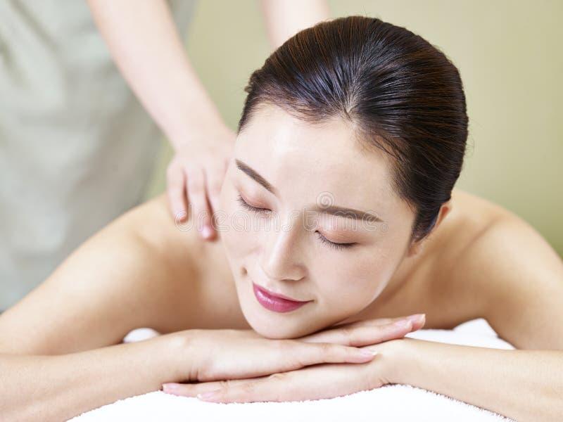 Mujer asiática joven hermosa que recibe masaje en salón del balneario foto de archivo libre de regalías
