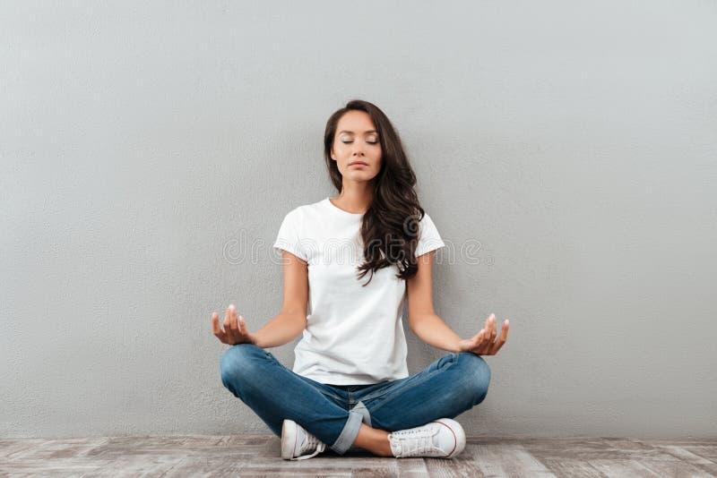 Mujer asiática joven hermosa que se sienta en la posición y meditar de la yoga foto de archivo