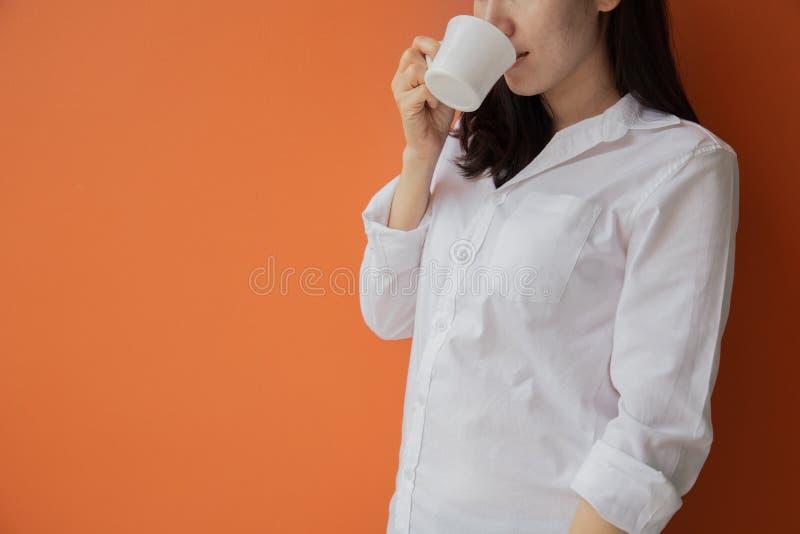 Mujer asiática joven que bebe la bebida caliente, café, té en fondo anaranjado aislado imagen de archivo libre de regalías