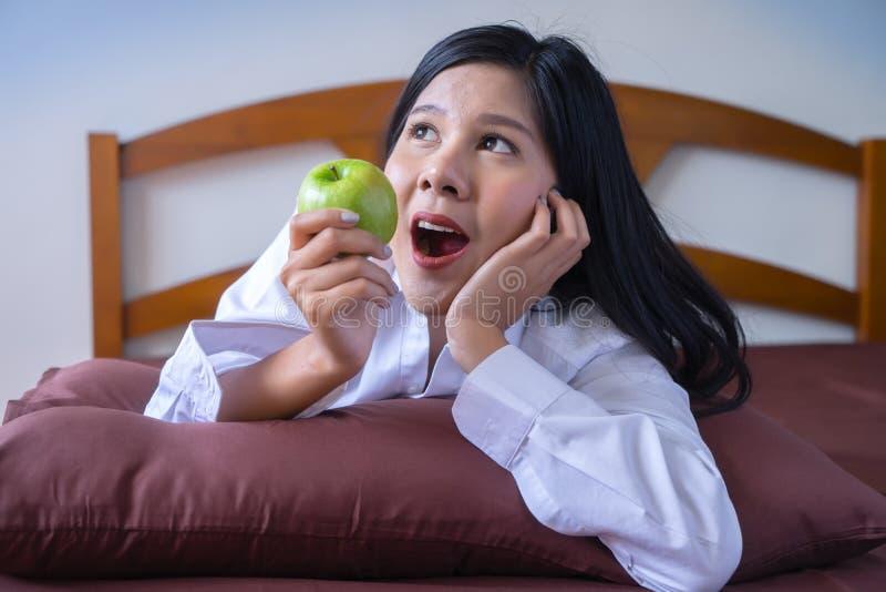 Mujer asiática joven que come la manzana verde en cama por mañana fotos de archivo libres de regalías