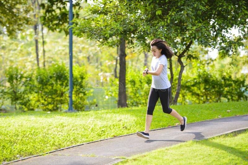 Mujer asiática joven que corre en un parque y miradas de la ciudad en el reloj elegante fotos de archivo libres de regalías