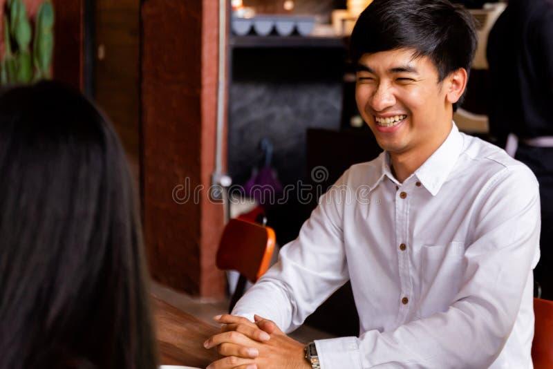 Mujer asiática joven que da una sonrisa preciosa y feliz a las mujeres para la primera fecha en restaurante del café imagen de archivo