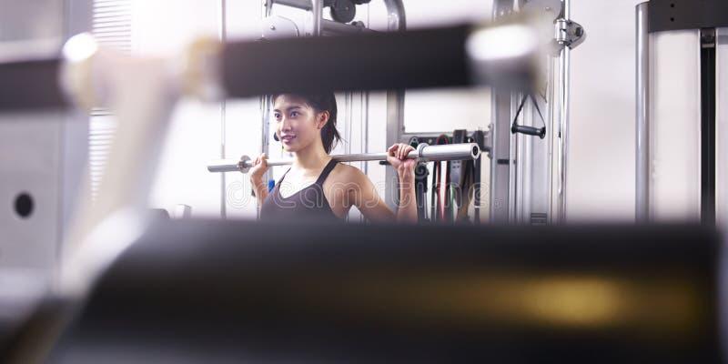 Mujer asiática joven que ejercita la elaboración en gimnasio imagen de archivo