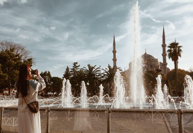 Mujer asiática joven que fotografía la mezquita azul con la fuente en el primero plano - Estambul imagen de archivo
