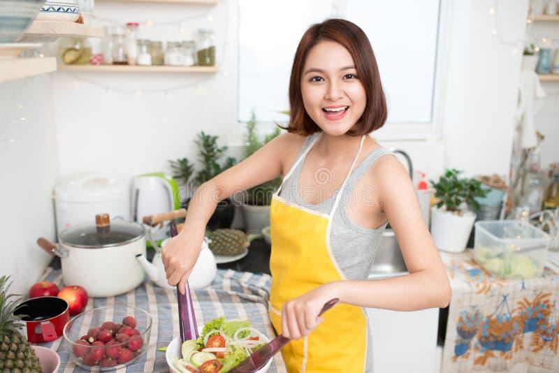 Mujer asiática joven que hace la ensalada en la cocina que sonríe y que ríe h imagenes de archivo