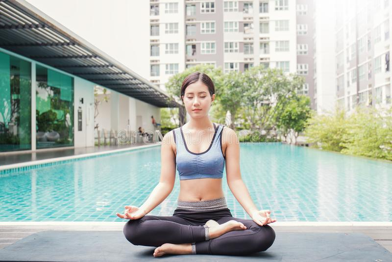 Mujer asiática joven que hace movimientos de la yoga o que medita por la piscina, fotos de archivo libres de regalías