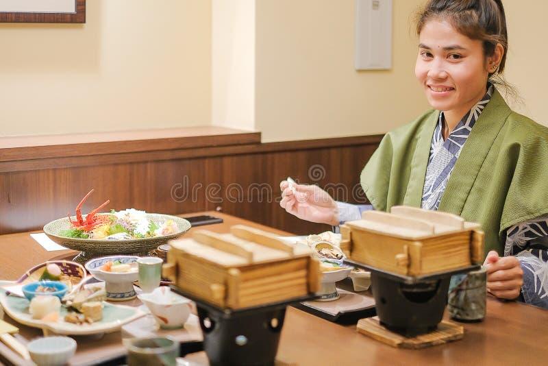 Mujer asiática joven que lleva Yukata con el sistema de cena y el aperitivo japoneses en la tabla de madera en centro turístico r foto de archivo libre de regalías