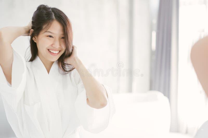 Mujer asiática joven que mira su cara en espejo en cuarto de baño imagen de archivo
