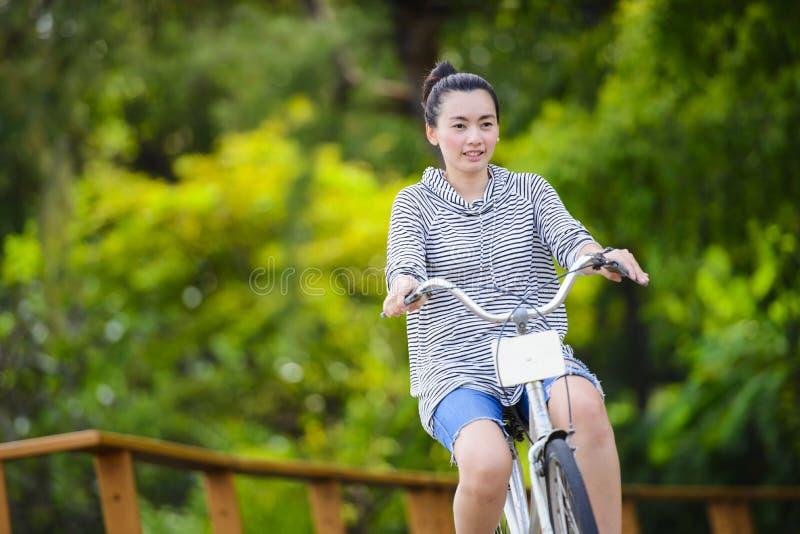 Mujer asiática joven que monta una bicicleta del vintage en un parque fotos de archivo