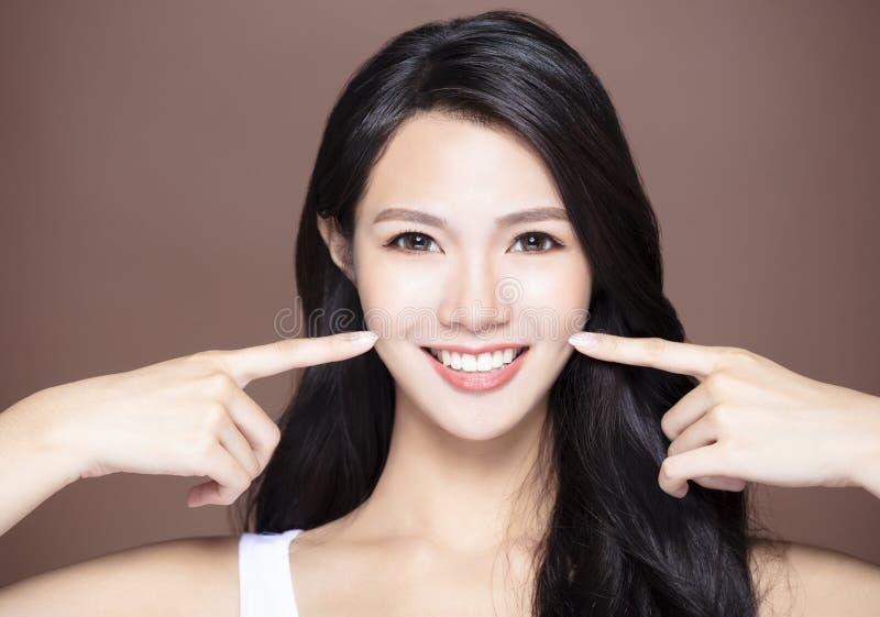 mujer asiática joven que muestra sus dientes fotos de archivo libres de regalías