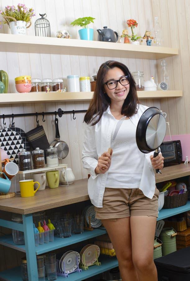 Mujer asiática joven que muestra una cacerola y una espátula en cocina fotos de archivo libres de regalías