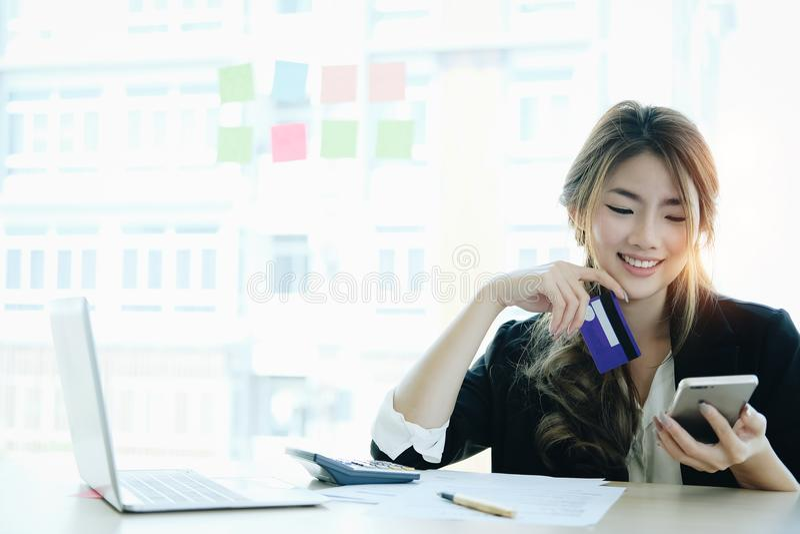 Mujer asiática joven que paga con la tarjeta de crédito en el teléfono elegante en casa foto de archivo