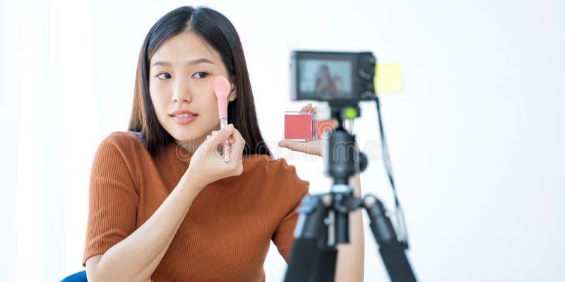 Mujer asiática joven que registra un vídeo para un blogger de la belleza de la mujer Tutorial del maquillaje foto de archivo libre de regalías