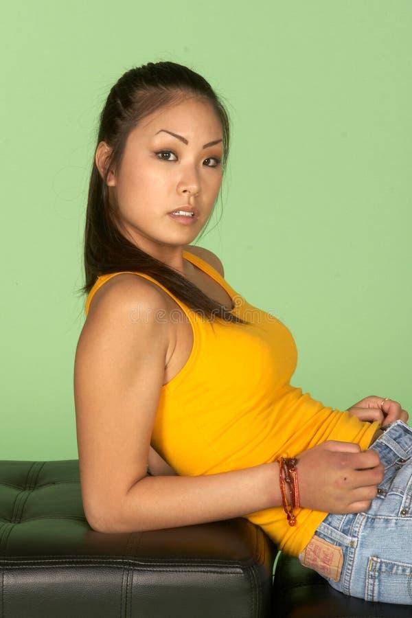 Mujer asiática joven que se inclina detrás en codos imagen de archivo libre de regalías