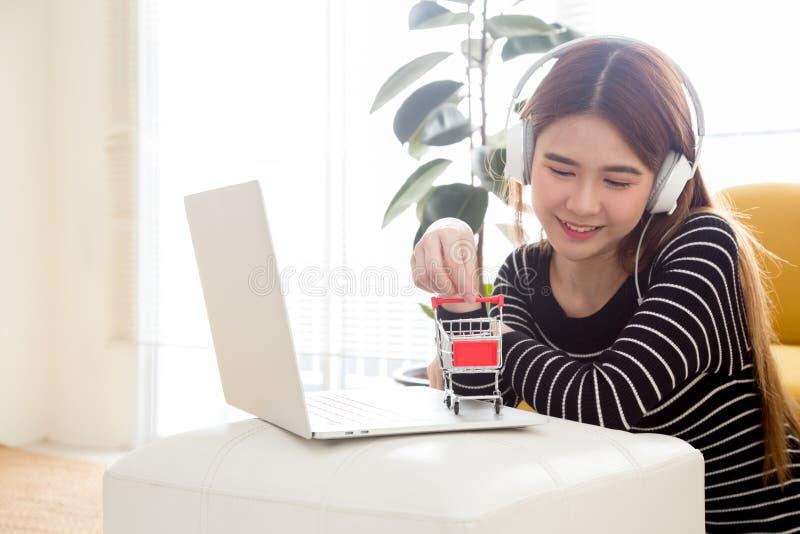 Mujer asiática joven que se sienta en el cuarto y que usa el ordenador portátil para las compras en línea y la música que escucha foto de archivo libre de regalías
